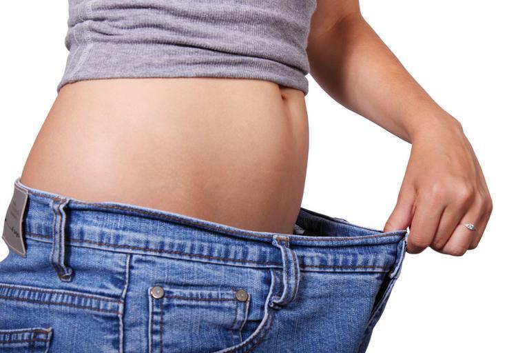 žena, která si drží kalhoty a je vidět jak zhubla